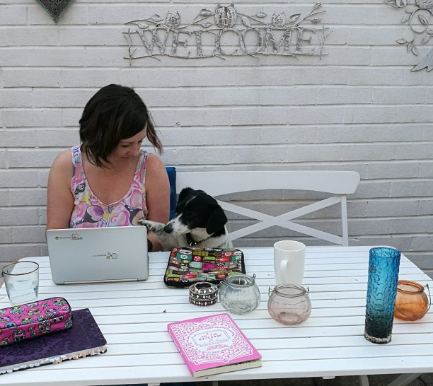 Lisette is sitting at a table in her back yard. On a white washed wall behind her it says Welcome. There is writing paraphernalia spread over the tile. Her little black and white rescue dog paws her hand while she's typing, offering editing advice.