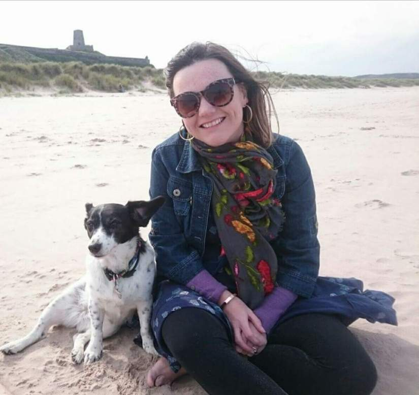 Lisette, a white woman with freckles and brown hair, is sitting barefoot on a beach. She is smiling widely and is wearing sunglasses, a scarf, denim jacket and blue dress with leggings. Harper Lee, her black and white little rescue dog sits and leans beside her, her ears are sticking up because it's windy. Bamburgh Castle sits behind them on the horizon.