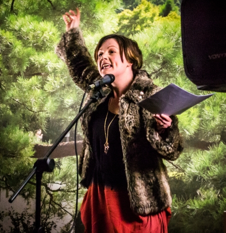photo description: Lisette stands on stage with a bright green leafy background, behind a mic, with arm outstretched looking ranty. photo credit: Ian Gibson