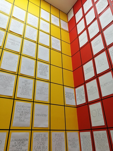 photo description: really high red and yellow walls with black grid outlines filled with white posters of words