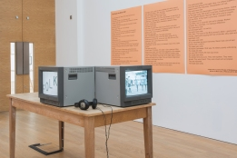 photo description: old fashioned square tv monitors are on a table in front of bright orange boards which have my poem printed on them