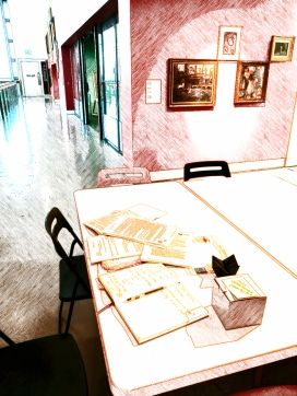 photo description: a sketch style photo of a table in a gallery covered in my written work