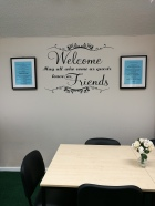 photo description: walls of a community centre which say welcome and on both sides of this are framed poems