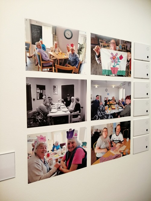 a set of six photos in a grid on a white wall in a gallery. They show members of the Creative Age projects showing off their craft work.