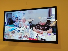 photo description: a TV screen image of three women working on crafts and drinking tea