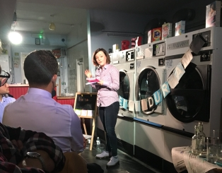 photo description: Lisette stands book in hand looking out at the audience. The backdrop is a row of washing machines hung with bunting.