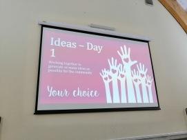 photo description: a big projector screen saying Ideas Day 1