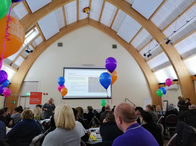 photo description: back of heads seated in full room with arched ceilings, staring at a huge projector screen with coloured balloons hanging in the air