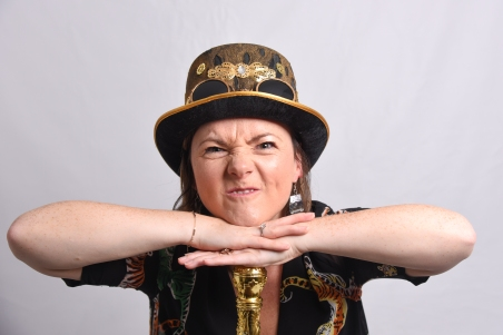 Lisette leans on a gold topped cane with scrunched up face wearing a steam punk top hat.