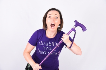 Image shows Lisette in a purple t-shirt which reads disability is not a bad word, holding her walking stick with her eyes and mouth wide open.
