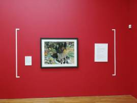 a bright red gallery wall with a vibrant painting of a landscape to the centre and my poem beside it