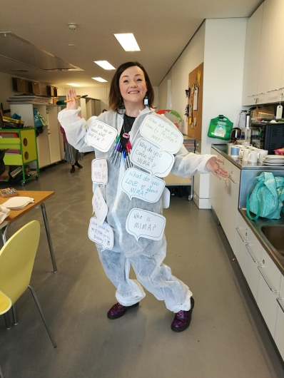 Lisette stands pen in hand with purple doc boots covered in red ladybirds. She is wearing a white boiler suit covered in giant word bubble questions such as - Who is MIMA?