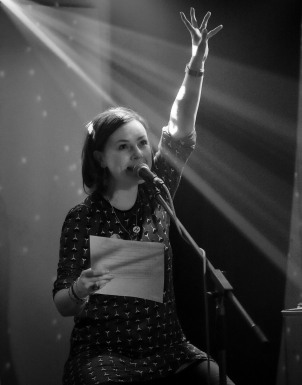 Black & white photo. Lisette sits on a stool on stage in front of a mic, spotlight on her, left arm reaching up.