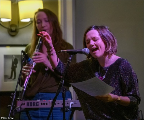 photo description: Lisette speaks in front of mic with Faye from Archipelago playing the clarinet in the background. photo credit: Ken Drew