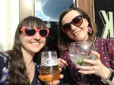 me and my sister, wearing sunglasses, saying cheers with beverages.