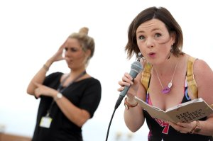 Lisette with mic and book saying 'Stay Focused + Extra Sparkly' pulling bizarre faces on a festival stage with comic book dress and gold hologram backpack.