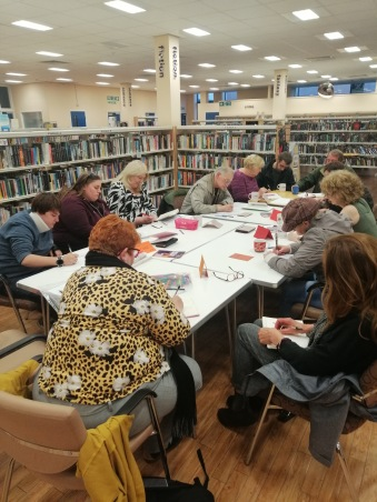 12 people sitting around a table in a library, all writing. So busy we had to pull out the emergency table!