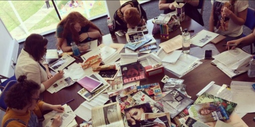 Young people around a table covered in magazines, all writing.