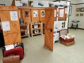 photo description - The Little Shed of Forgotten Dreams in an art gallery, a full sized shed covered with stories and images, filled with objects on shelves and with suitcases stacked outside.