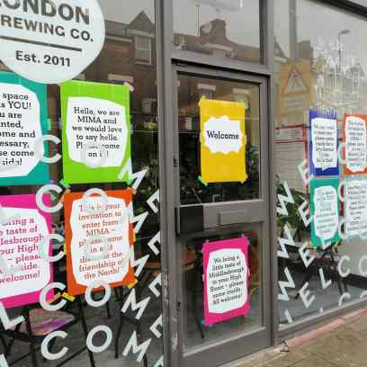 colourful welcome posters in our Walthamstow shop front
