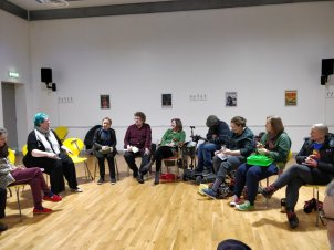 9 disabled artists, members of Disconsortia sit in a semi-circle. Some are laughing, everyone is focused. There are sticks and a scooter in view.