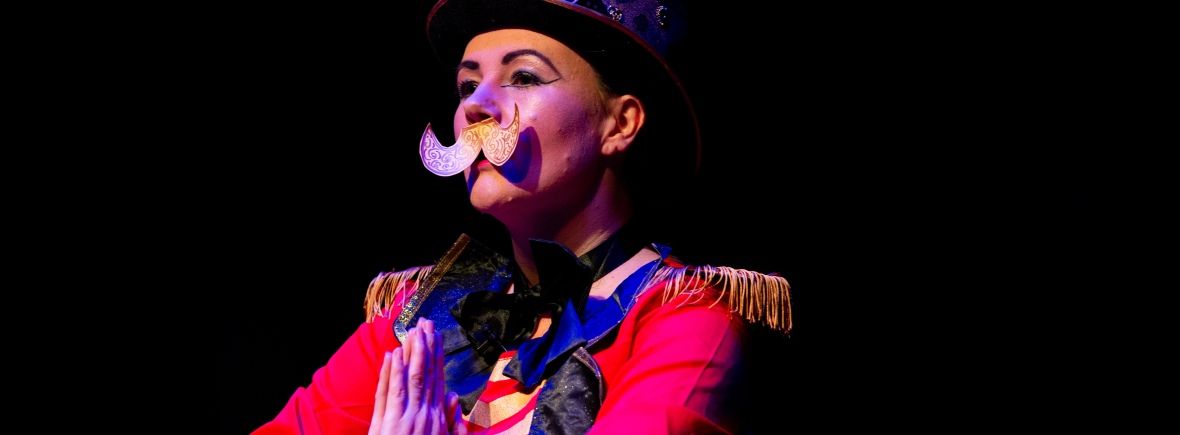 Lisette is wearing ringmistress costume, a top hat and a paper moustache. photo credit -taken at the Disconsortia DIY Cabaret by Kev Howard
