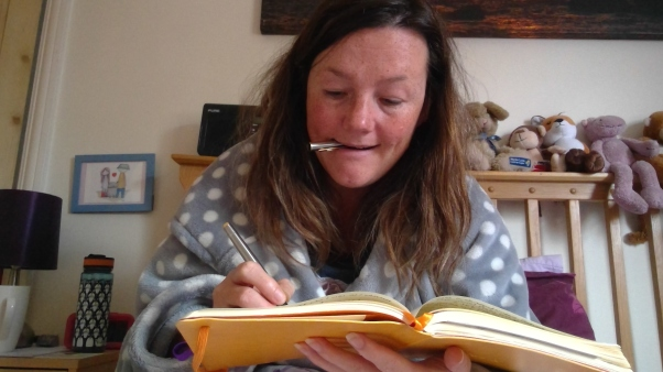 photo description: Lisette's hair is messy. She is wearing her dressing gown and is working in bed. Soft toys on the headboard behind her, a bedside table with penguin covered water bottle, an alarm clock and a lamp. She has a pen top in her mouth, she is holding her pen and concentrating on writing in a yellow notebook.