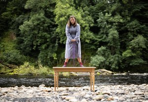 photo description: Lisette, a white woman with freckles and long brown hair, stands on top of a wooden table. She is wearing a grey dressing gown, purple Dr Marten boots and leaning on a purple perspex walking stick. The table is on a pebble beach with a river running behind it, with lots of green trees. image credit: Rob Irish