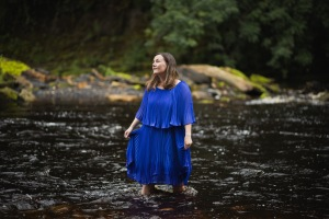 photo description: Lisette is wearing a flowing blue dress. She is standing in a river, and holding her skirt. She gazes off to the side. image credit: Rob Irish