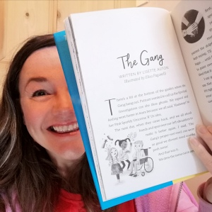 image description: Lisette grins to the point her face may fall off, and holds The Puffin Book of Big Dreams open at her story - The Gang. Illustrated by Elisa Paganelli.