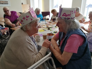 photo description: older women sit around a table crafting. Two women at the centre hold each others hands and sing.
