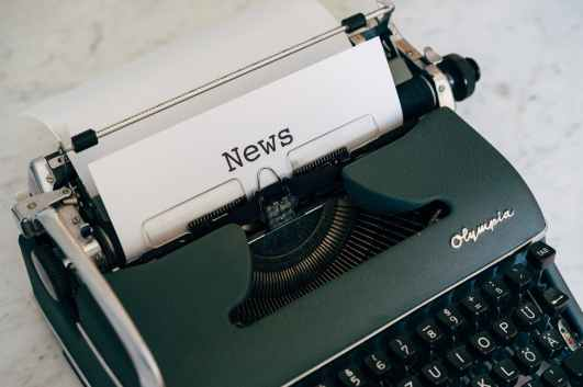 Photo by Markus Winkler - an old Olympia typewriter containing a sheet of paper which says 'News'