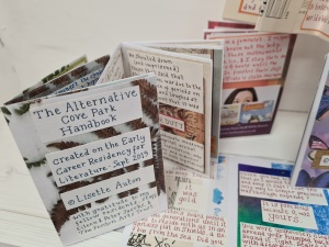 photo description: 6 handmade multicoloured little instant books, most blurry, to the Foreground The Alternative Cove Park Handbook which is blue handwriting on a background of photocopied leaves