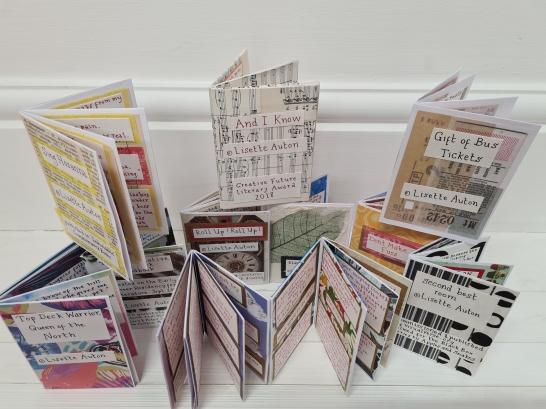 photo description: a stack of eleven handmade multicoloured little instant books