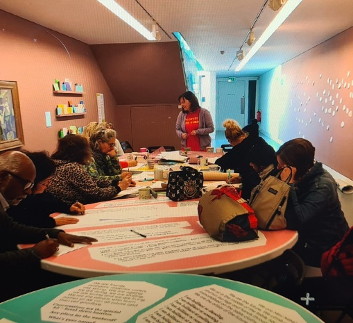 photo description: Me conducting a writing workshop at MIMA with members of Cloth Club who are all sitting around circular tables in bright pastel colours, the tops of which are printed with quotes from my lyrical essay.