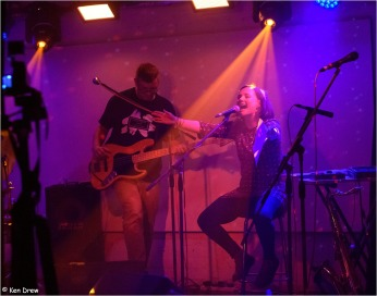 Lisette sitting behind a microphone, shouting, arms outstretched. John Pope on bass guitar behind. Stage lit in pinks and purples.